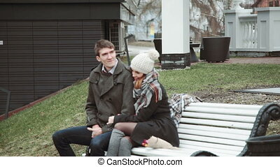 Romantic Young couple sitting on a white bench, in a coat...