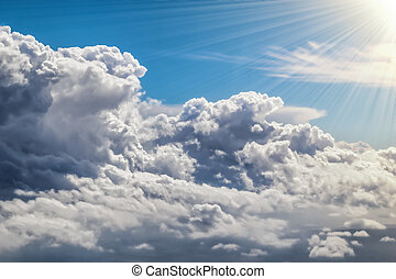 Big fluffy clouds with bright summer sunshine and blue sky background.
