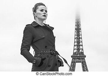 young woman standing against Eiffel tower in Paris, France -...