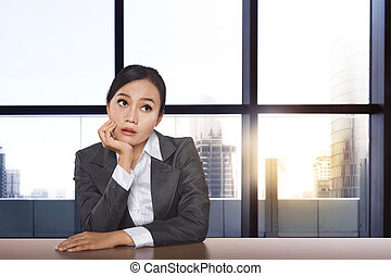 Stressed asian businesswoman thinking the solution while working