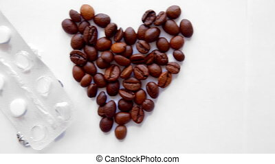 pills and heart from coffee beans on white background