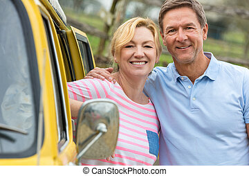 Happy Middle Aged Man and Woman Couple With Camper Van Bus