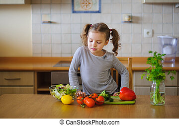 Cute girl of younger school age cuts vegetables and greens...