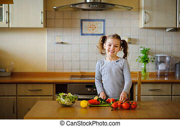 Girl 8-9 years old in the kitchen slicing vegetables for a...