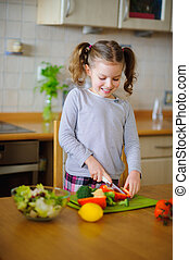 Little cook cooks salad. On a table various vegetables....