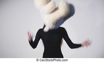 young woman catches a teddy bear on a white background