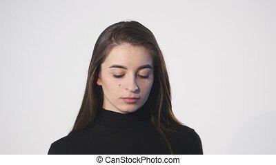 Close up of woman on her cellphone against a white background