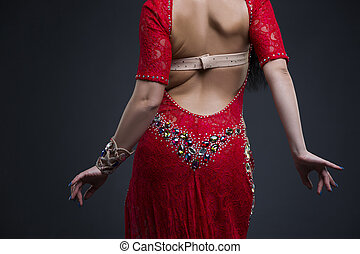 Young beautiful exotic eastern women performs belly dance in ethnic red dress with open back on gray background