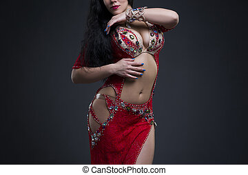 Exotic eastern women performs belly dance in ethnic red...