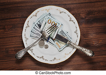 A plate with a few hundreds dollars on the wooden background