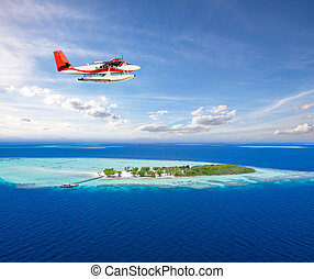 Seaplane flying above small tropical island on Maldives,...