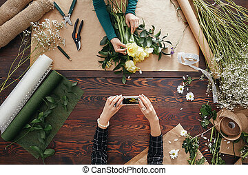 Woman taking a picture of a bouquet - Woman taking a picture...