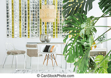 White dining room with communal table and green plant