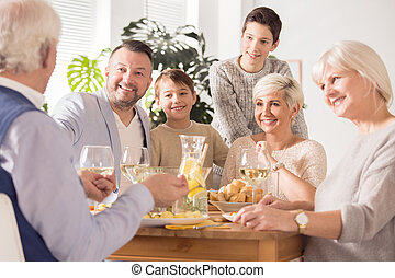 Family spending time together, eating and talking beside...