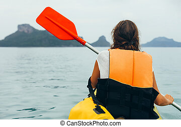 Back view of young woman kayaking in sea on background of...