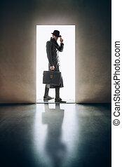 Man silhouette standing in the light of opening door in dark...