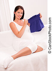 Beautiful pregnant woman holding baby clothes