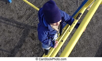 Little kid climbing up on ladder in playground - Little kid...