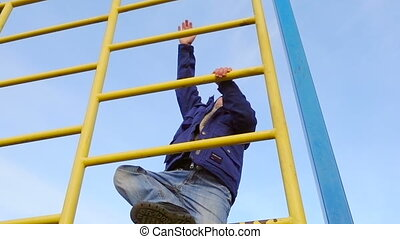 Little kid climbing on ladder in playground against blue sky