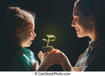 Adult and child holding green sprout.
