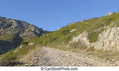 Mountain Biking - Mountain biker who is driving downhill on...