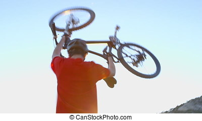 Mountain biker lifting his bike and holding it over his head...