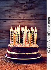 birthday cake with many lit candles - a cake topped with...