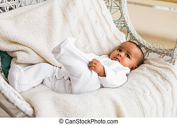 adorable african american baby boy indoors lying