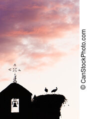 Bell tower with storks. - Bell tower with two storks in the...