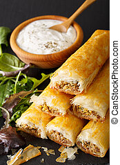 Filo rolls briouats with meat, eggs and greens close-up and...