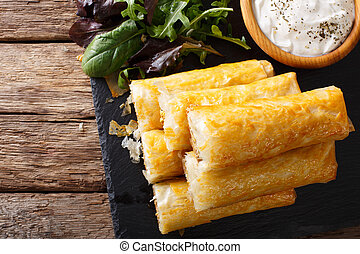 Filo rolls with meat, eggs and greens close-up and yogurt....