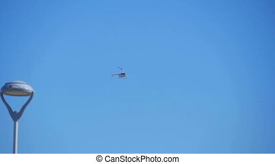 Business white Helicopter in blue sky, slow-motion