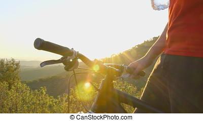 Mountain biker taking a break, drinking some water from a...