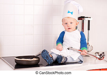 Little baby chef in the cook hat with metal ladle