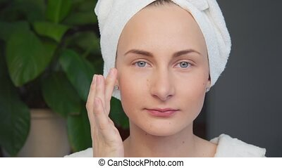 Portrait of beautiful woman applying cream on her face