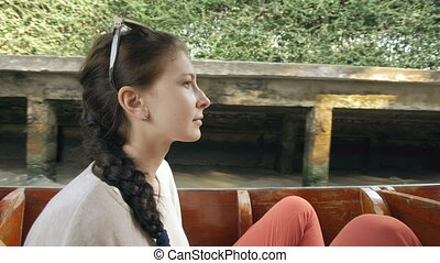 Young woman tourist ride wooden boat in flaoting market in Thailand and photographing ethnic people