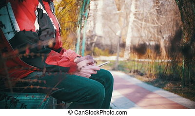 Young Man using a Smartphone on a Bench in the City Park -...