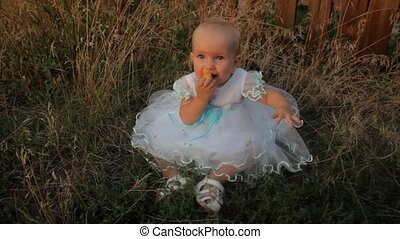 A baby girl sitting in the high grass in a white dress and eating an apricot. A little boy sits near her and takes her hand. Sunset in summer.