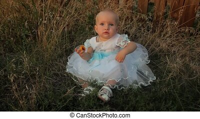 A baby girl sitting in the high grass in a white dress, eating an apricot and starts tear grass near her. Sunset in summer.