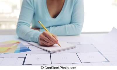 woman with blueprint drawing interior to notebook -...