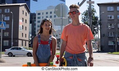 teenage couple with penny boards walking in city - summer...