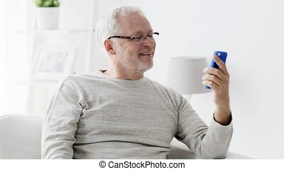 senior man having video call on smartphone at home -...