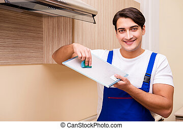Young man working with kitchen equipment