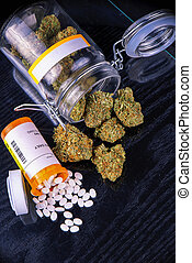 Cannabis buds and prescriptions pills over black surface -...