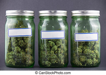 Cannabis glass jars over grey background - medical marijuana...
