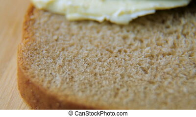 the knife spreads butter on black bread. Close up