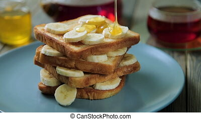 Fresh homemade crispy toast with honey and bananas on blue...