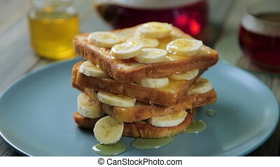 Fresh homemade crispy toast with honey and bananas on blue plate. Delicious breakfast.
