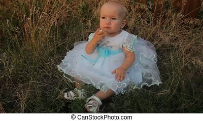 A baby girl sitting in the high grass in a white dress. She gnaws an apricot. Sunset in summer.