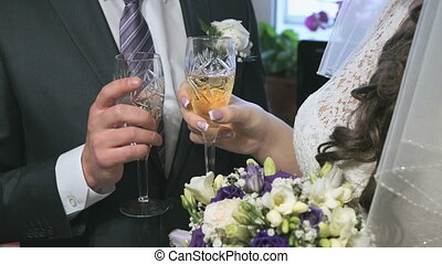 Bride and groom holding glasses of champagne and clink their...
